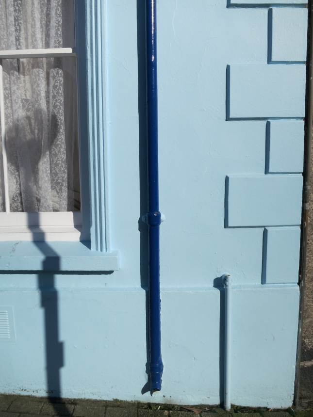 Blue drainpipe and Belisha beacon shadow