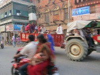 Family on a scooter and young men on a tractor, moving in opposite directions