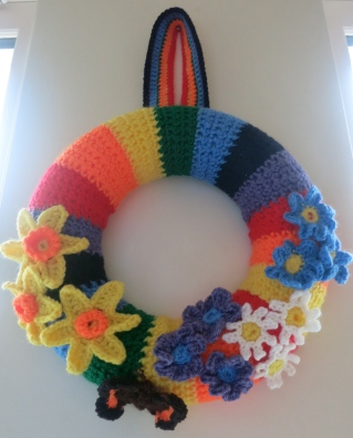 Crocheted rainbow wreath with spring flowers