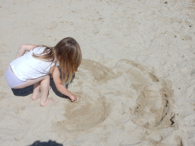 Adding a face to her sand-angel - in all her 'sandy glory'