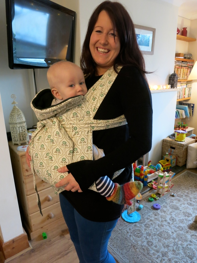 The baby carrier tied round the baby's middle