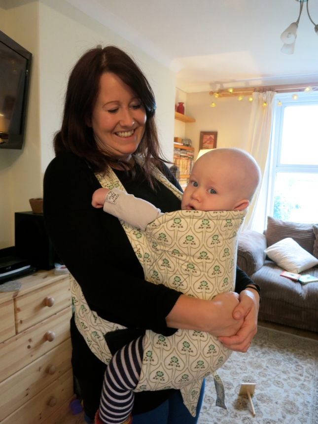 The baby carrier tied underneath the baby