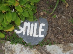 One of the stones around the gardens, saying Love, Peace, Rest and Smile