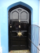 Beautiful front door in Penzance , note the bend in the metal grid so that the handle can be reached